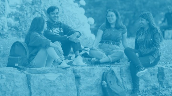 four people talking while sitting on rocks